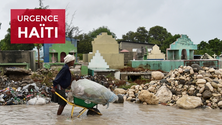 A woman pushes a wheelbarrow while walking in a partially flooded street, in the Haitian capital, Port-au-Prince, on October 4, 2016. Hurricane Matthew made landfall in southwestern Haiti early Tuesday, crashing ashore as a powerful Category Four storm, US weather forecasters said.""