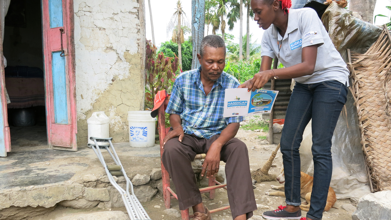 Séance de sensibilisation aux risques de catastrophes par Handicap International en Haïti (photo d'archive); }}